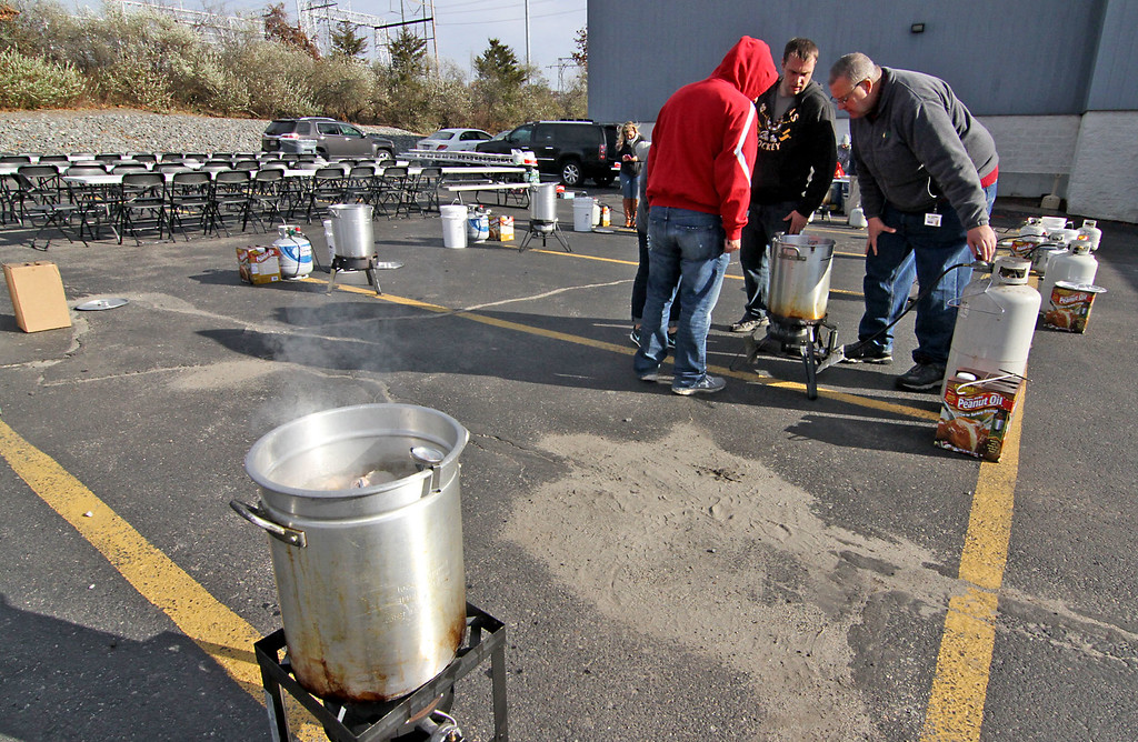 . Checking the temp of the hot oil before placing a turkey in the pot is L-R, Joe Basile, David Basile, (both family members that own Catania Oil) and Gary Groleau, IT Manager for Catania Oil. SUN/David H. Brow