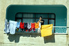 A woman on a balcony hangs laundry up to dry in rural Turkey, Eurasia.