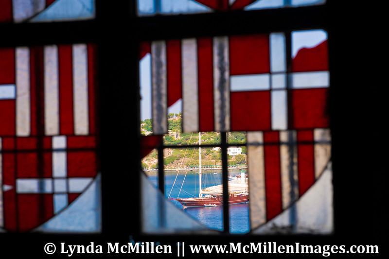 Boat on harbor seen through broken stained glass window.