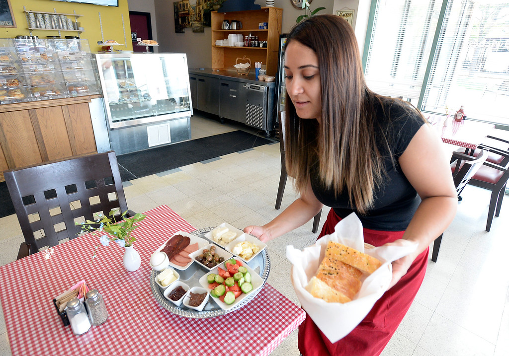 . Boulder, CO - AUGUST 16: Selda Cayir, owner, brings out main course at Breakfast Champion Mediterranean Breakfast, Lunch and Bakery. (Photo by Cliff Grassmick/Staff Photographer)