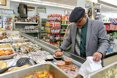 Cote's Market, on Salem Street in Lowell, is celebrating a century in business this year and is now in its fourth generation. Elkin Montoya, 56, tries to figure out what he would like for lunch at the market on Friday afternoon. SUN/JOHN LOVE
