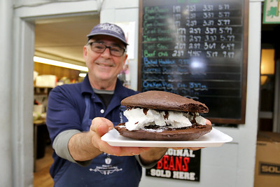 Cote's Market, on Salem Street in Lowell, is celebrating a century in business this year and is now in its fourth generation. Owner Roger Levasseur shows off one of their Black moon pies or some times called whoopie pie. SUN/JOHN LOVE