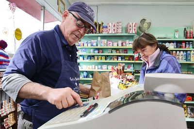 Cote's Market, on Salem Street in Lowell, is celebrating a century in business this year and is now in its fourth generation. Owner Roger Levasseur rings up a customer on Friday afternoon. SUN/JOHN LOVE