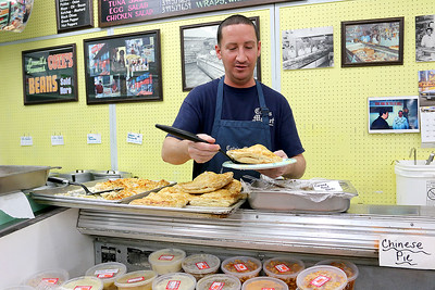 Cote's Market, on Salem Street in Lowell, is celebrating a century in business this year and is now in its fourth generation. Owner Kurt Levasseur works on Friday at the market. SUN/JOHN LOVE