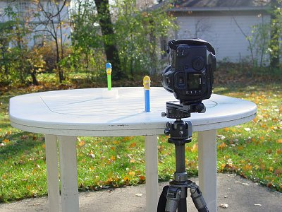 Our willing test targets set firmly <i>(they're taped down!)</i> on a table. Initially, they should line up perfectly while your camera is pointed straight ahead. One is very near; the other about a meter farther away. The rear target is a little higher up so I could see both in the viewfinder.