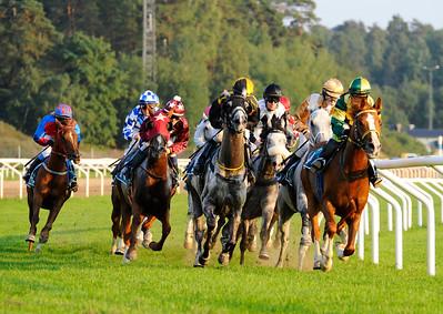 Hästarna på väg in i järnvägskurvan med varvet kvar | WATHBA STUD FARM CUP | Täby 110827 Foto: Stefan Olsson / Svensk Galopp