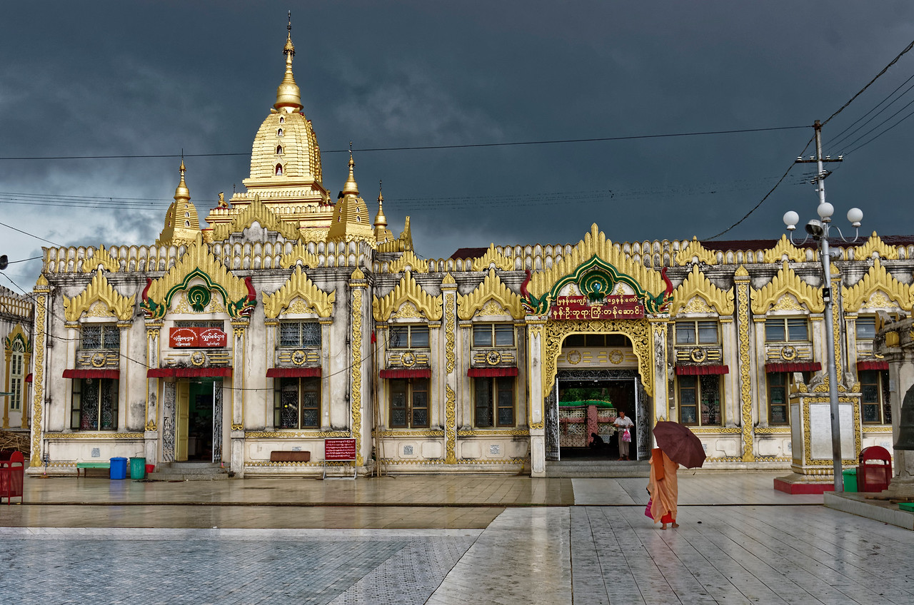 A monk is caught in a tropical rainstorm as he heads for cover at Botahtaung Pagoda.
