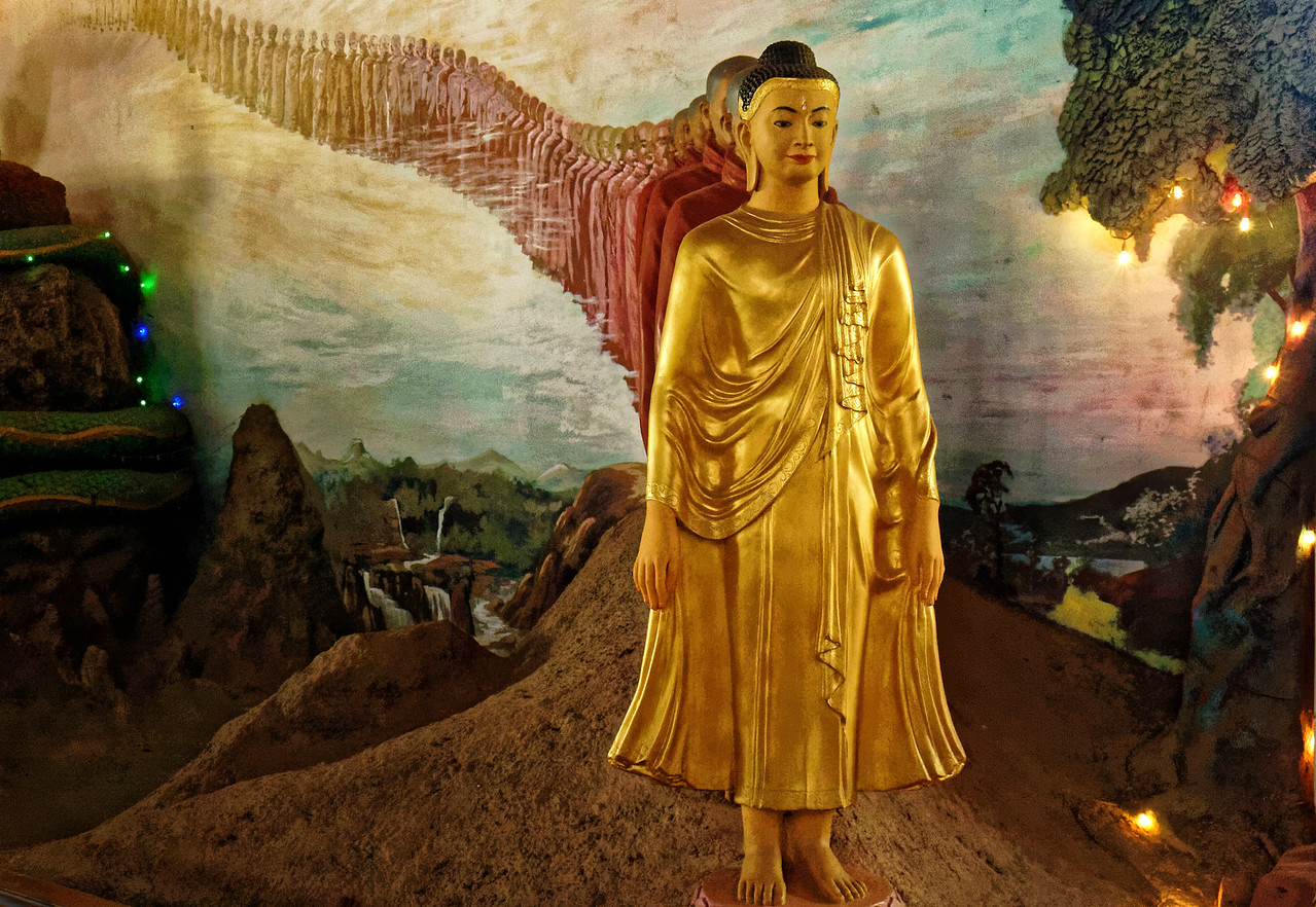 A sculpted Buddha at Nga Htat Gyi seems to emerge from a mural with an endless line of followers.