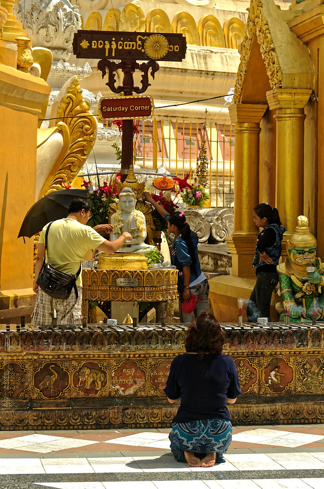 These worshippers were making merit by pouring holy water on the Buddha sculptures. A shrine is provided for each of the days of the week, and worshippers seek out the one that corresponds to the day on which they were born.