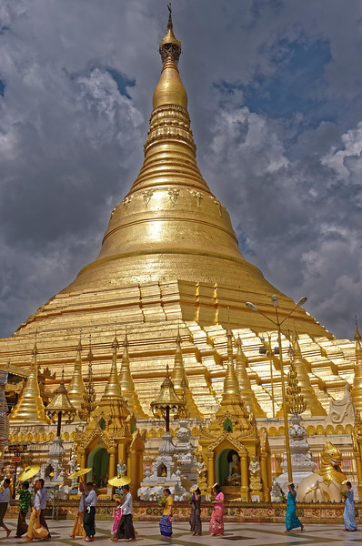 Worshippers are dwarfed by the size of the main stupa or pagoda itself.