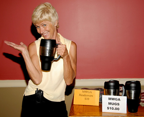 Tournament site Director, Peg Seifner, uses her best sales pitch for MWGA items.