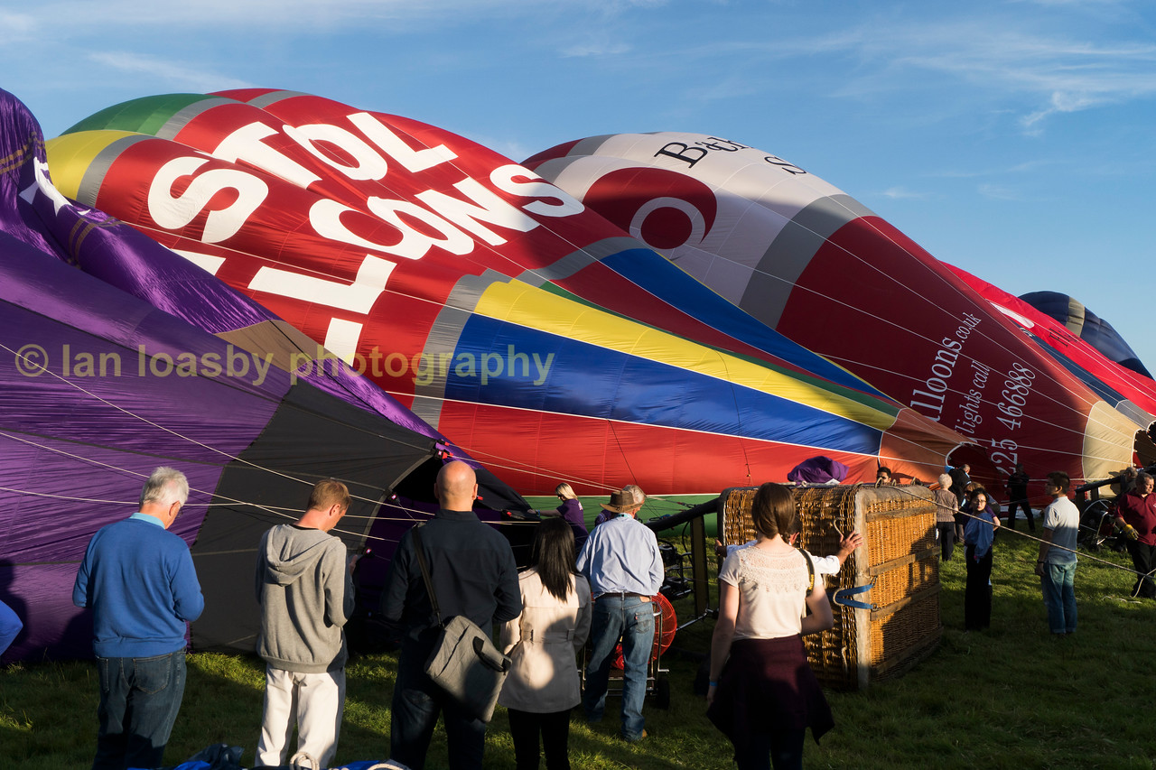 passengers and invited guests look on as the balloons are inflated