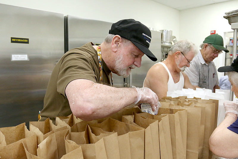 Roger Downing, 81, works on filling the bags for the meals on wheels as he volunteers at the Tyngsboro Council on Aging Monday, June 26, 2017. SUN/JOHN LOVE