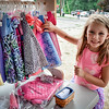 Katherine Benecchi of Chelmsford looks through some handmade doll clothes made by Creative Threads of Hudson at the Tyngsboro Farmers Market on Saturday. SUN/Caley McGuane
