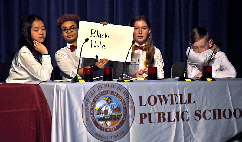 Lowell team member Nina Wolf holds up correct answer to one of the questions, next to her on right is Gabby Rudy 14, and Jackson Little 12. SUN/David H. Brow