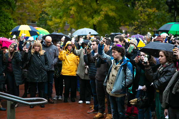 Vigil atendees at the University of Michigan hold up their phone flashlights as the names of each victim is read aloud on October 28, 2018.
