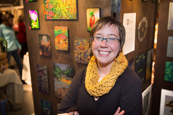 Andrea Dirheimer of Visionary Images Photography smiles for the camera while displaying her work at the UICA Holiday sale.