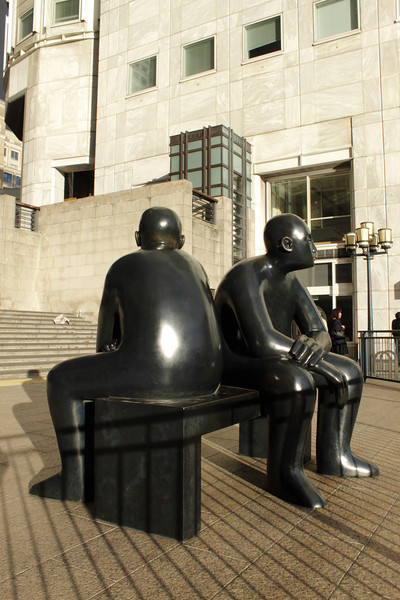 Statues of people sitting on bench Canary Wharf Docklands London
