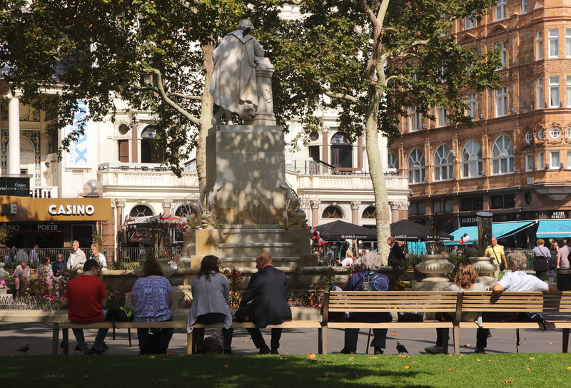 People relaxing near the William Shakespeare Statue Leicester Square London September 2017