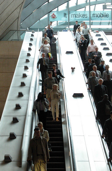 Commuters descending escalator at Canary Wharf London