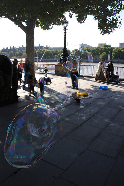 Street entertainer blowing soap bubbles South Bank London September 2009