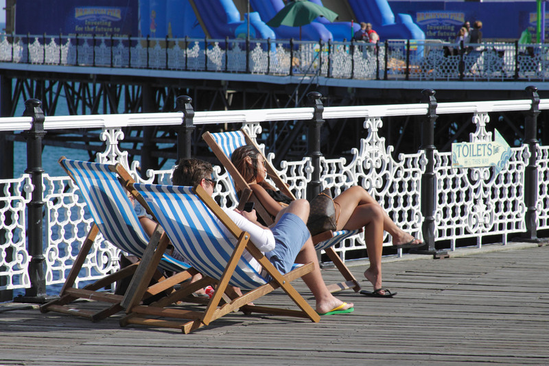People relaxing on deck chairs on Brighton Pier Sussex