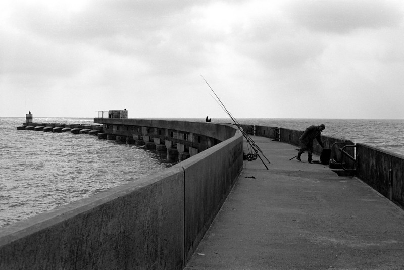 Sea fishing on sea wall at Brighton Sussex