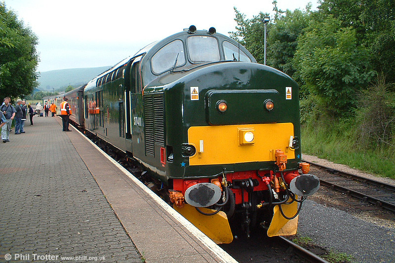 Carrying its 1960s-era BR green livery, celebrity EWS class 37 37411 stands at Rhymney with the 0959 from Cardiff on 25th June 2005.