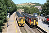 Two trains, one passenger: units 158826 and 150279 pass at Ferryside Station on 24th July 2006.