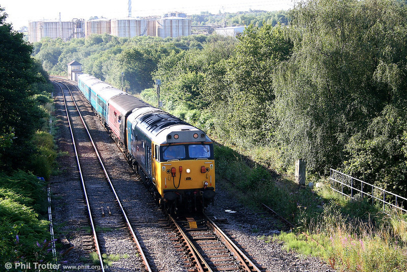 Class 50 sunrise: 50049 'Defiance' at Llandarcy, Swansea District Line, with the 0728 Cardiff - Llandrindod Wells on 24th July 2006.
