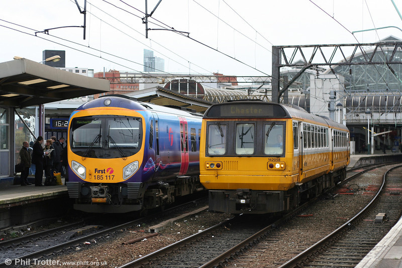 contrast in dmu styles! Northern's Merseyrail liveried 142058 departs Manchester Piccadilly with the 1624 service for Chester, passing TPE's 185117 waiting with the 1420 Barrow-in-Furness to Manchester Airport. 8th March 2007.