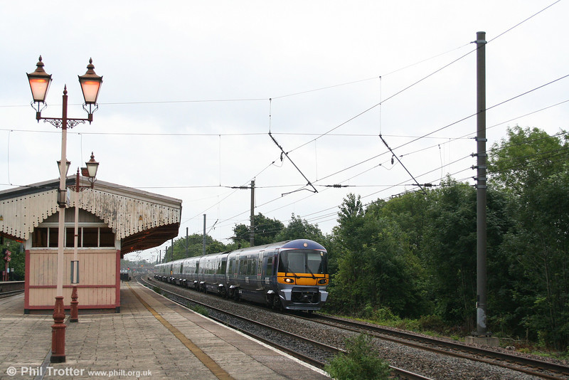 332013 contrasts with the traditional features of Hanwell Station as it passes with the 1655 Paddington - Heathrow Airport on 5th July 2007.