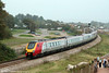 Four-car 221141 leads the 0857 Derby to Paignton past Langstone Rock on 30th August 2008. 47773 and 33025 wait in the loop at Dawlish Warren.