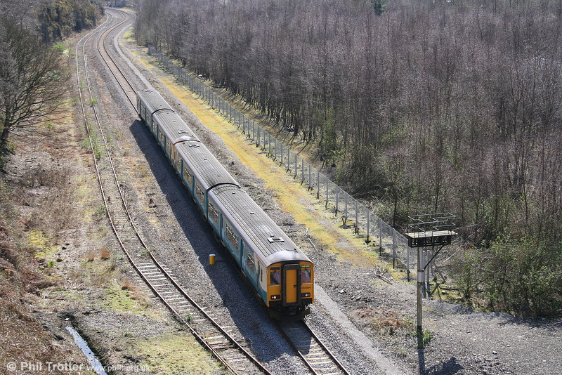 150284 and 150252 forming the 1235 Cardiff Central to Ebbw Vale at Aberbeeg on 22nd March 2008. The disused signal bracket is a reminder that the wooded area to the right was once the site of Aberbeeg Yard.