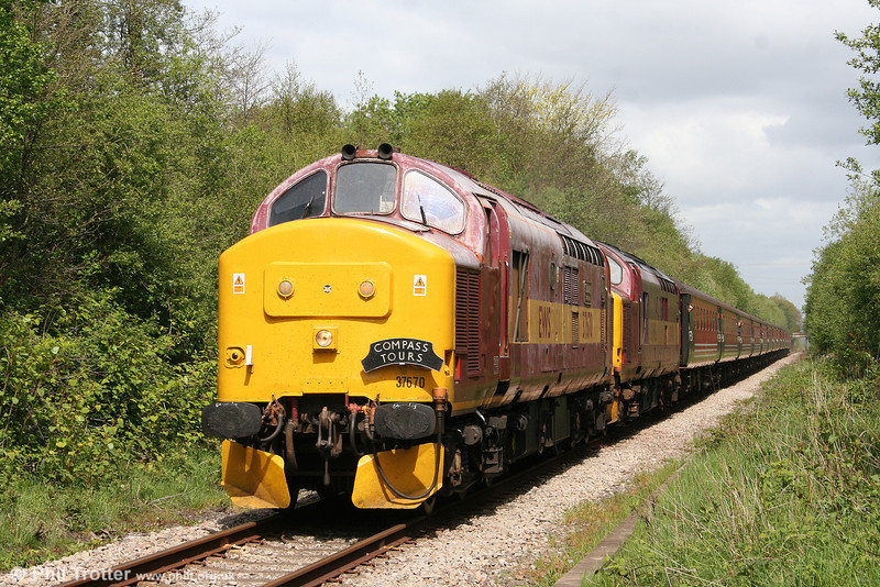 Recently reinstated 37670 'St. Blazey T&RS Depot' and 37401 approach Pontarddulais with Compass Tours 1Z51, 0713 Mossley Hill to Cardiff Central, 'The Heart of Wales Scenic Rambler' on 2nd May, 2009.