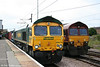 66574 passes 66001 at Peterborough with 4E24, 1039 Thamesport to Leeds on 4th August 2009.