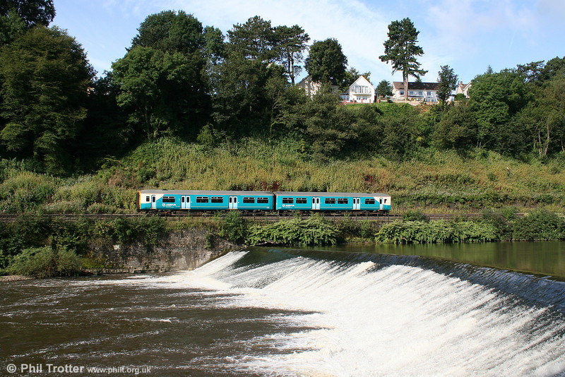 The substantial rainfall of the previous few days has swollen the River Taff; ATW's 0908 Merthyr Tydfil to Barry Island passes Radyr Weir on 29th August 2009.