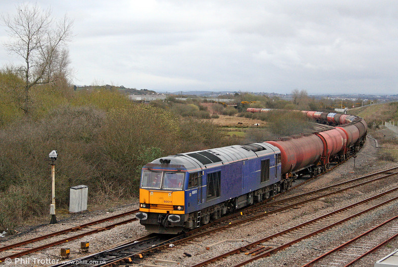In less than ideal lighting conditions, Mainline blue 60011 joins the West Wales main line at Llandeilo Junction with 6B07, 1800 Margam to Robeston on 30th March 2009.