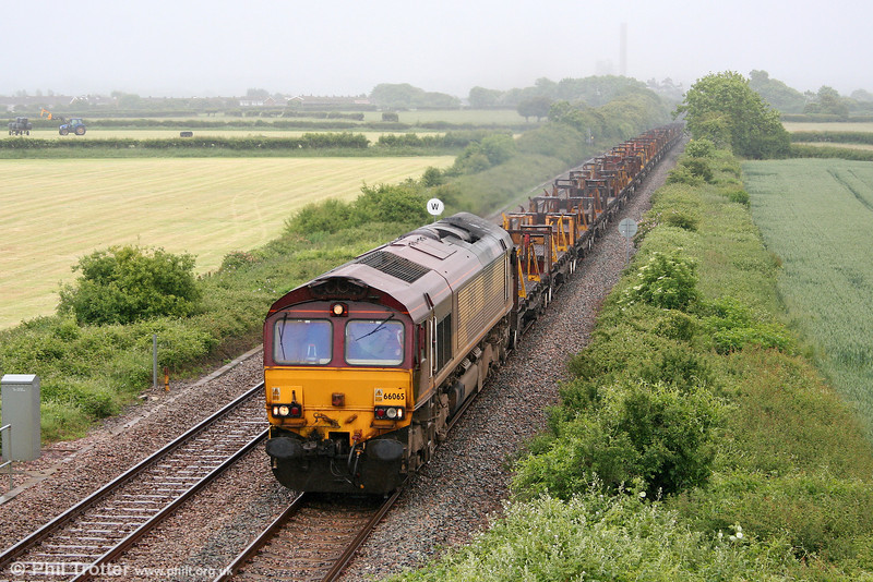 A sudden change in the weather finds 66065 passing St. Athan in full drizzle with 6V50, 1500 Llanwern to Margam on 13th June 2010.
