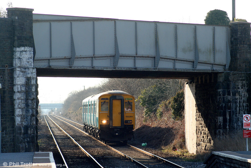 150264 approaches Bynea forming the 1516 Swansea to Shrewsbury on 7th March 2010. The white painted bridge abutment (left) was to aid visibility of the semaphore signals which once stood at the end of the platform.