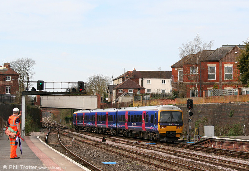 The look-out acknowledges the driver of 166220 as it calls at Newbury forming the 1136 Bedwyn to London Paddington on 9th April 2010.