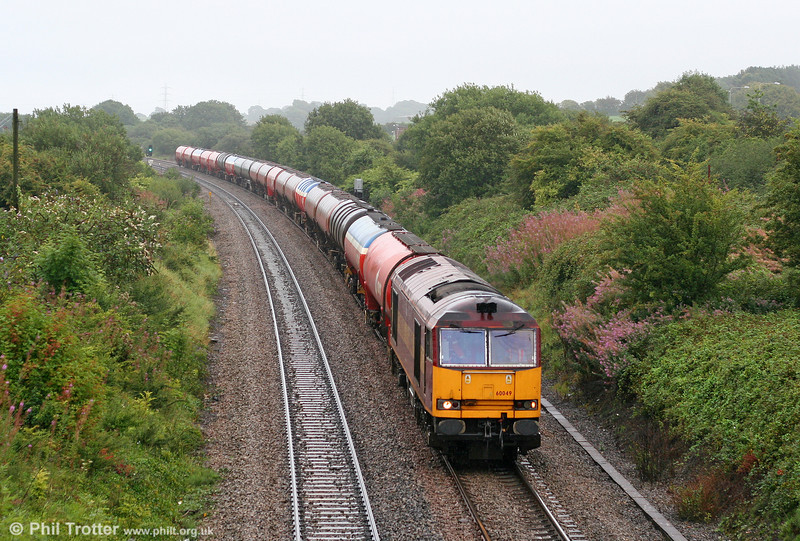In familiar August weather, 60049 passes Pyle with August 21st's 6B33, 1212 Theale to Margam fuel empties. The earlier Pyle station once stood at this location, offering connections to Tondu and Porthcawl; it closed in 1964.