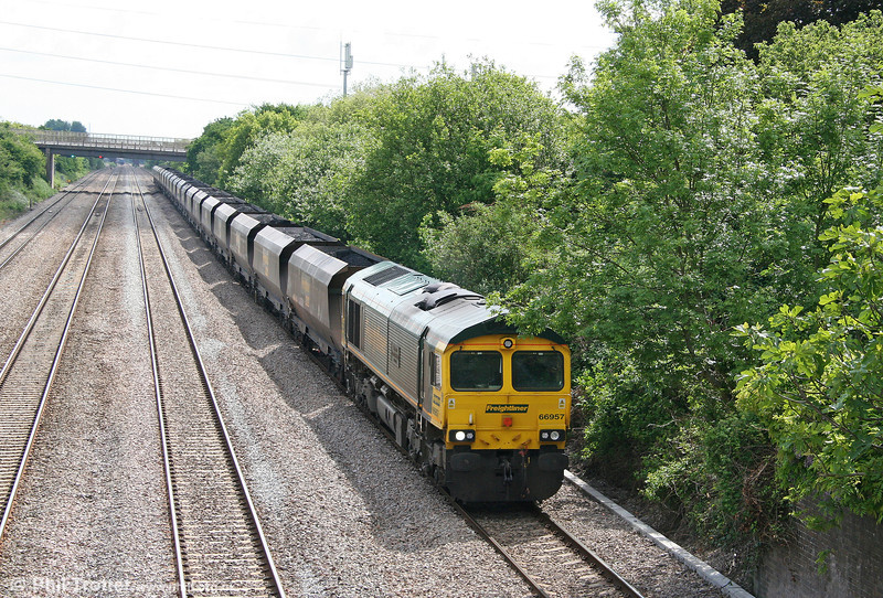The overhanging trees at Llandevenny which have annoyed photographers for several years are now encroaching on the down relief line. The highest numbered FLHH class 66, 66957 'Stephenson Locomotive Society' pushes past with 6M61, 0825 Portbury to Rugeley Power station on 28th May 2010.