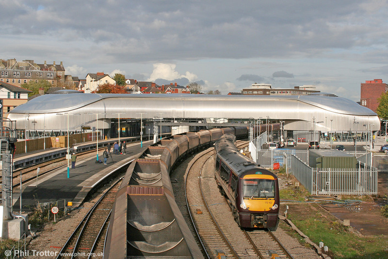 Newport's new £22m station building looks more than a little incongruous amongst more traditional architecture. XC 170102, forming the 1208 Nottingham to Cardiff Central, passes a rake of empty HTAs on 30th October 2010.