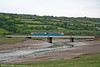 A class 143 unit, forming the 1605 Swansea to Pembroke Dock, crosses the Gwendraeth Fach at Kidwelly on 5th June 2010.