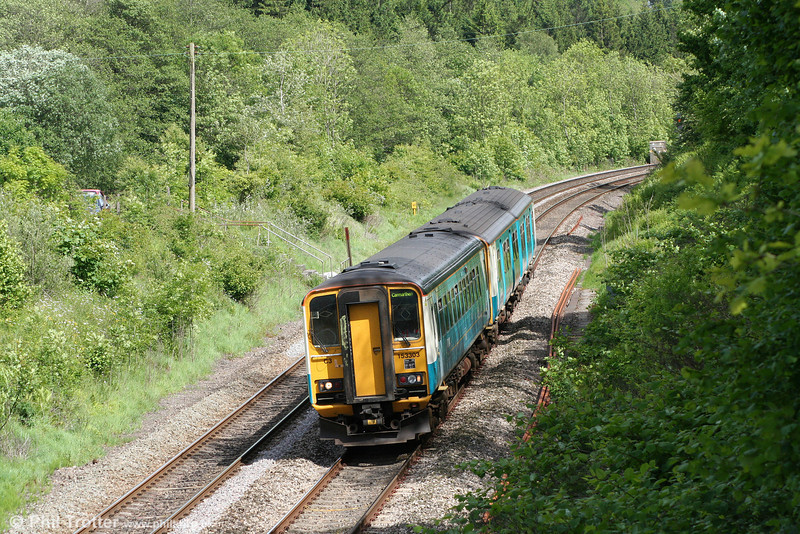 153303 leads a class 150 near Llanharan forming the 1438 Newport to Carmarthen on 14th May 2011.