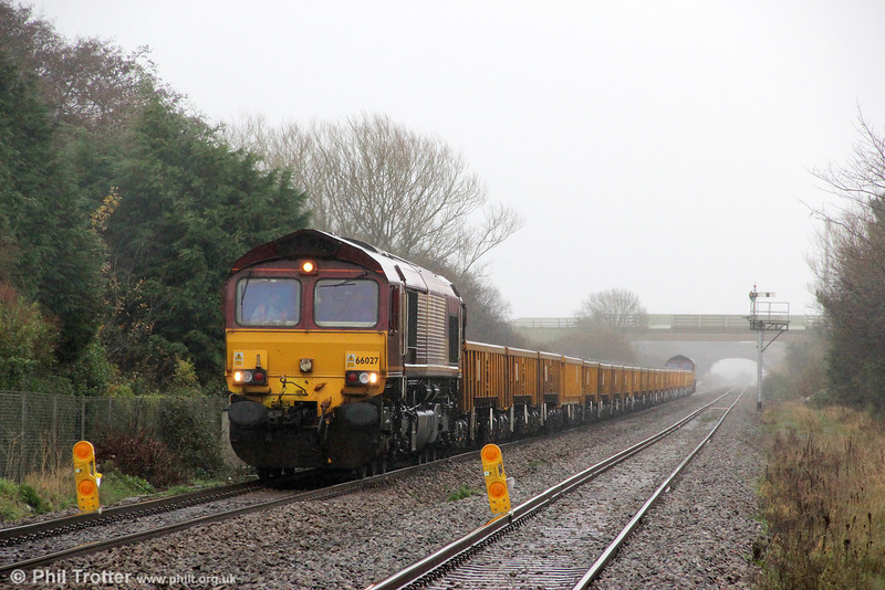 In connection with track relaying on the down main at Pembrey, 66027 waits on the up road at Pembrey Crossing with a load of new ballast on 11th December 2011. With 66021 at the rear, the train was 6W02 from Newport, ADJ.