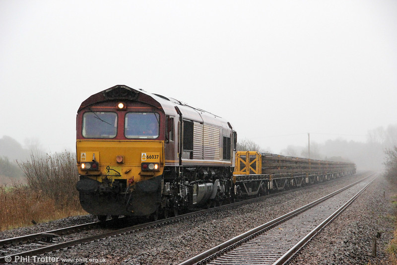 66037 sits in the pouring rain on the up road near Penybedd Crossing with 6W01 and a load of used track panels on 11th December 2011.