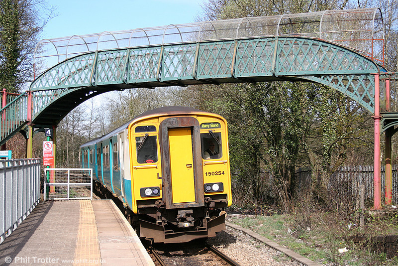 150254 calls at Penrhiwceiber forming the 1122 Aberdare to Barry Island on 2nd April 2011. The footbridge is of Taff Vale Railway origin.