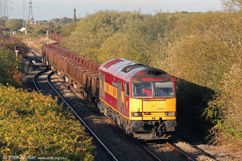 The appearance of a non-overhauled class 60 is becoming something of a novelty! Here, 60045 'The Permanent Way Institution' departs from Trostre Works with a lengthy rake of empties forming 6B61, 1105 Trostre to Margam on 21st October 2012. The ivy clad chimney in the background is a remnant of the former Morfa Brickworks.